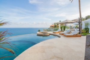 infinity pool with lounge chairs in private waterfront villa in cabo