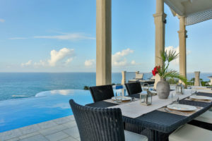 outdoor dining overlooking infinity pool in a waterfront private villa in saint lucia